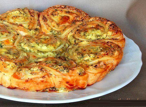 Хотите немного вкусненького? Наивкуснейший закусочный пирог, который легко можно разобрать на порционные булочки-завитушки! Ингредиенты: 250 грамм дрожжевого слоеного теста, 200 грамм мягкой феты (брынзы), 1 маленькое яйцо, 1 желток, 2 столовых ложки жирной сметаны, 2 зубчика чеснока, свежая зелень (укроп, петрушка, тархун, кинза), 2 столовых ложки сливочного масла, 1 столовая ложка сливок, перец, сухой майоран