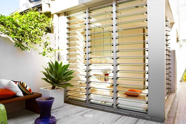 Let the light and the breeze in with louvres. Also note the sunken bath in the bathroom behind, with a floating sink and toilet this creates more space.