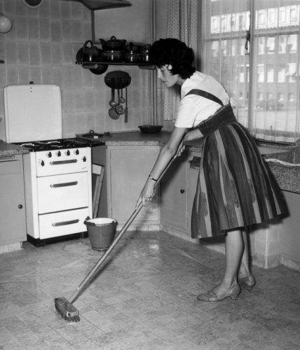 Schrobben van de keukenvloer. Huisvrouw schrobt de tegelvloer met harde borstel op steel en emaille emmer met sop, in een keuken met granieten aanrecht, gasfornuis, pannenrek en lepelrek. 1959.