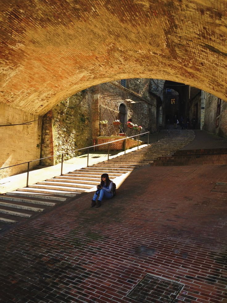 Girl under arch bridge in Perugia, Italy