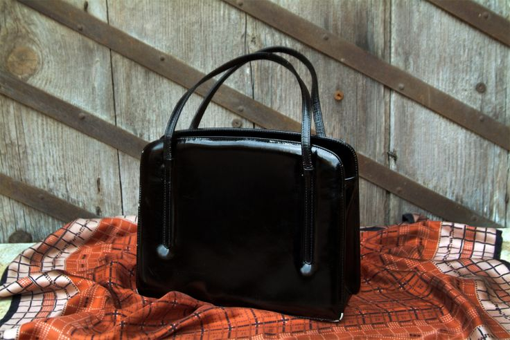 Original 1960s vintage leather bag, painted in glossy black. Interior lining with contrasting red leather and interior pockets. Snap closure with button type clutch.http://www.vitrinevintage.com/product-details.php?id=3616