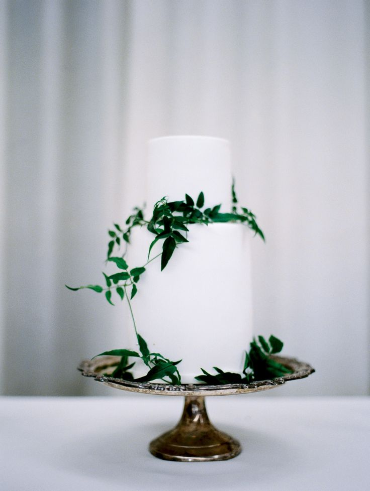 elegant white cake adorned with greenery | Photography: Czar Goss