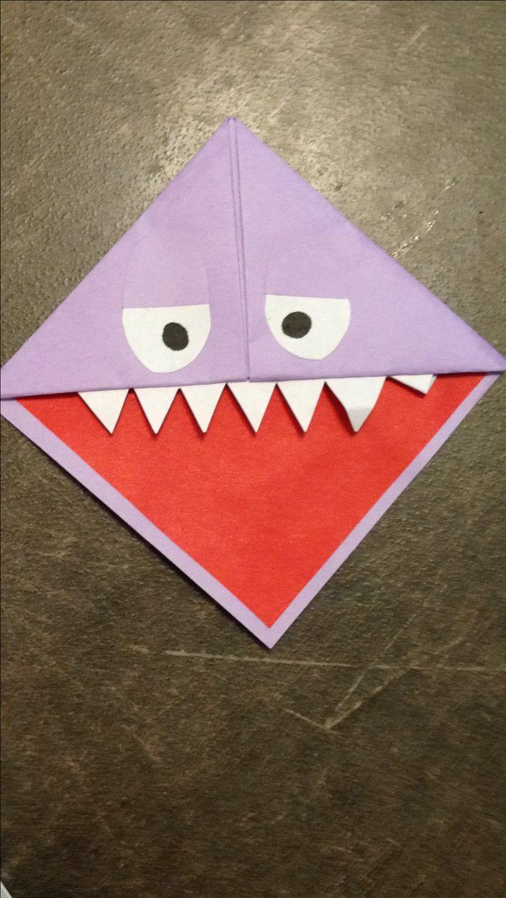 Monster boekenlegger van papier. Vierkante vouwblaadjed gebruikt. Zie instructie elders voor vouwen. Net een truitje. Tong is iets kleiner vierkantje. Tanden zijn een wit strookje. Zwart van de ogen is getekend met een stift.
