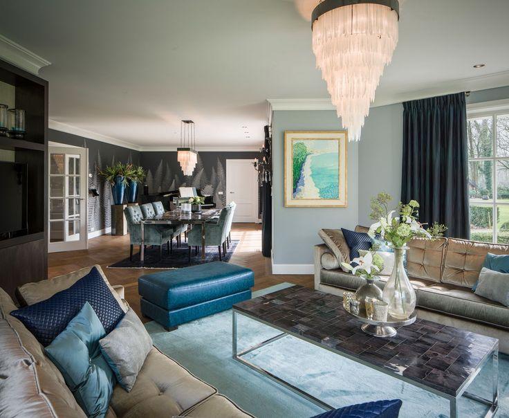 Stijlvolle woonkamer met piano. Blauwe accenten karakteriseren de woonkamer. Let op de chique kroonluchter! - Maison La Plume