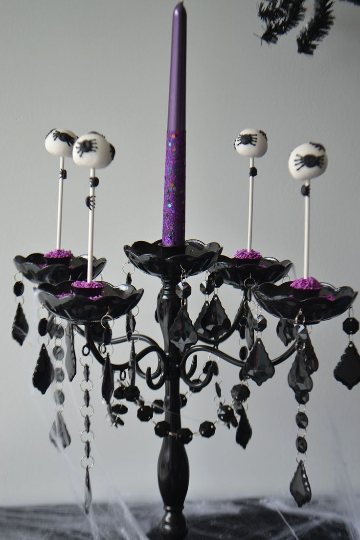 Spider Cake Pops in a black candelabra. Perfect for a spooky Halloween Dessert Table. By Bake Sale.