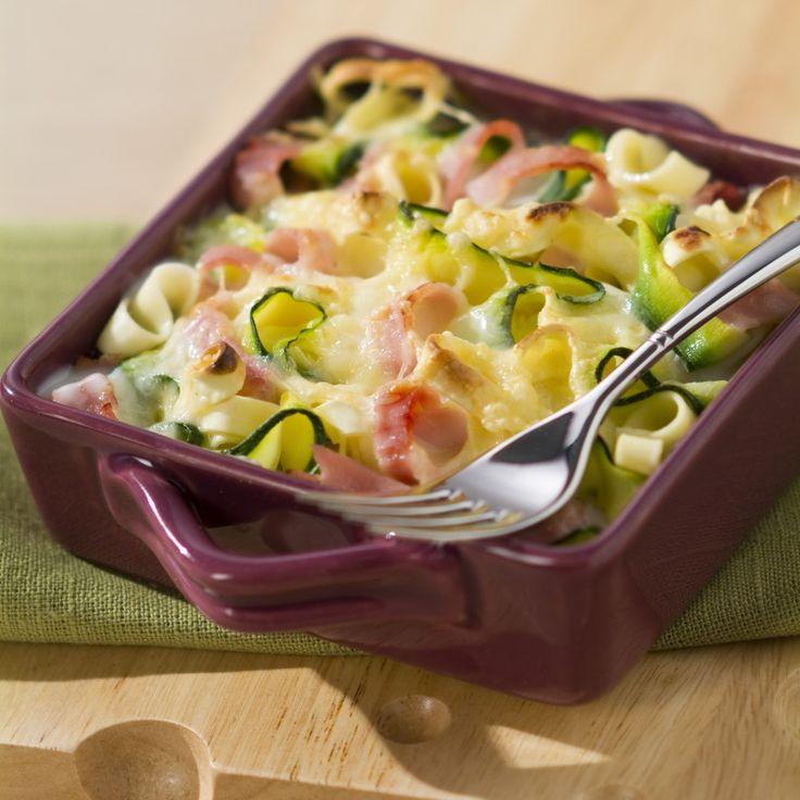 """Préchauffezvotre four en position gril. Lavez les courgettes. A l'aide d'un couteau économe, découpez des rubans de courgettes pour obtenir des """"tagliatelles"""". Faites cuire les tagliatelles de courgettes environ 2 minutes dans l'eau bouillante puis ajoutez les tagliatelles de """"pâtes"""" et prolongez la cuisson de 3 minutes. Egouttez et versez dans un plat à gratin. Découpez les tranches de jambon en longues lamelles, type tagliatelles et déposez-les dans le plat."""