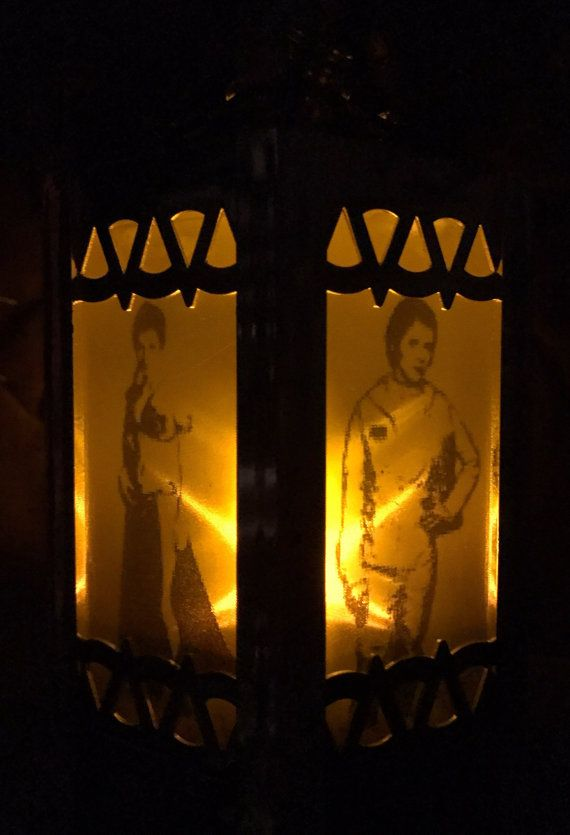 Princess Leia Tribute Gold Mini Battery-Operated Plastic Lanterns  Tribute to Everyones favorite Princess! How she changed our lives. These adorable lanterns make perfect gifts. These cute little lanterns, can also be used for Fish Extender Gifts, Theme Weddings, Christmas Trees decorations, Nightlights, the possibilities are endless!  This Lantern is inspired by a Princess Leai Character and used in silhouette form. Each lantern has 6 sides and can be fully customized to your needs. The…