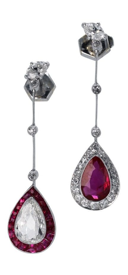 A pair of Art Deco platinum, ruby and diamond pendant earrings, circa 1920. Designed as alternating pear-shaped pendants, one set with a pear-shaped diamond framed by 20 calibré rubies, the other pendant set with a pear-shaped ruby framed by 18 old European-cut diamonds, each pendant supported from knife-edge links spaced by 6 old European-cut diamonds. #ArtDeco