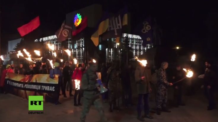 """Ukrainische Nationalisten und Rechtsradikale sind gestern mit Fackeln auf die Straßen der Innenstadt von Tscherkassy gezogen, um den """"Tag des Verteidigers der Ukraine"""" zu markieren, der von Petro Poroschenko 2014 auf den 14. Oktober, dem Jahrestag der Gründung der Ukrainischen Aufständischen Armee (UPA), per Dekret vor versetzt worden war. Die UPA kollaborierte im Zweiten Weltkrieg zeitweilig mit Hitler und war an Massentötungen von jüdischen und polnischen Zivilisten beteiligt.    ..."""