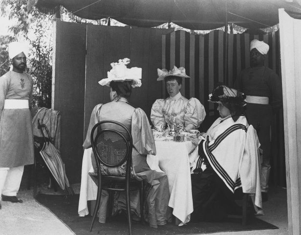 Seated at a table outside, under a canopy: Beatrice, Pss Henry of Battenberg, seen from behind; Pss Helena Victoria of Schleswig-Holstein, facing camera; Queen Victoria, profile left. Sheikh Ghulam Mustafa and Sheikh Chidda in attendance.
