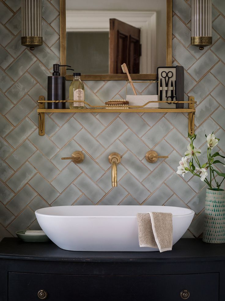 Brass fittings with a warm lustre and tiles with a shimmering finish evoke Parisian Art Deco allure. Mint half tiles, ceramic, 6x13cm, £119.95sq m, The Winchester Tile Company, www.winchestertiles.com. Cheltenham bathroom wall lights in Antiqued Brass, H28.5xW8.5xD11.5cm, £157 each; Chiswick mirror in Antiqued Brass, 44x65cm, £125; Pembroke shelf in Old Gold, H16xW63cm, £73.50; all Jim Lawrence, jim-lawrence.co.uk.