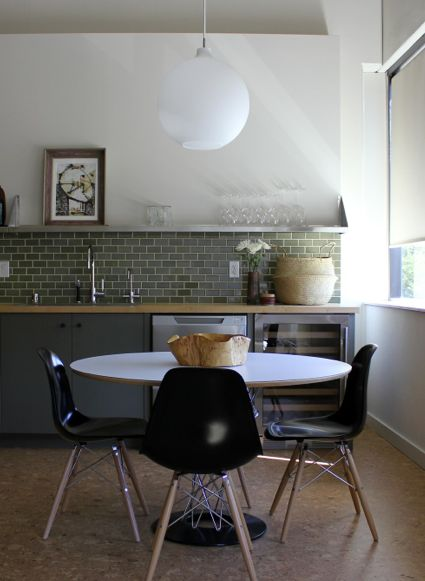 globe pendant + light green subway tile + stainless steel shelf detail + pedestal table in kitchen by disc interiors