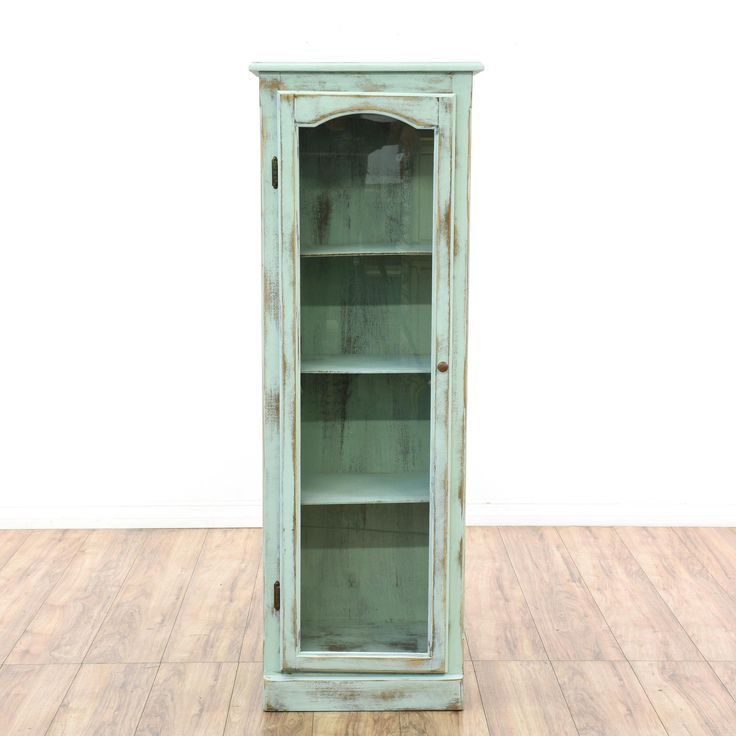 This shabby chic display cabinet is featured in a solid wood with a distressed light blue chalk paint finish. This curio cabinet has a glass front door with an interior case and shelving. Great for displaying books and knick knacks! #shabbychic #storage #bar #sandiegovintage #vintagefurniture