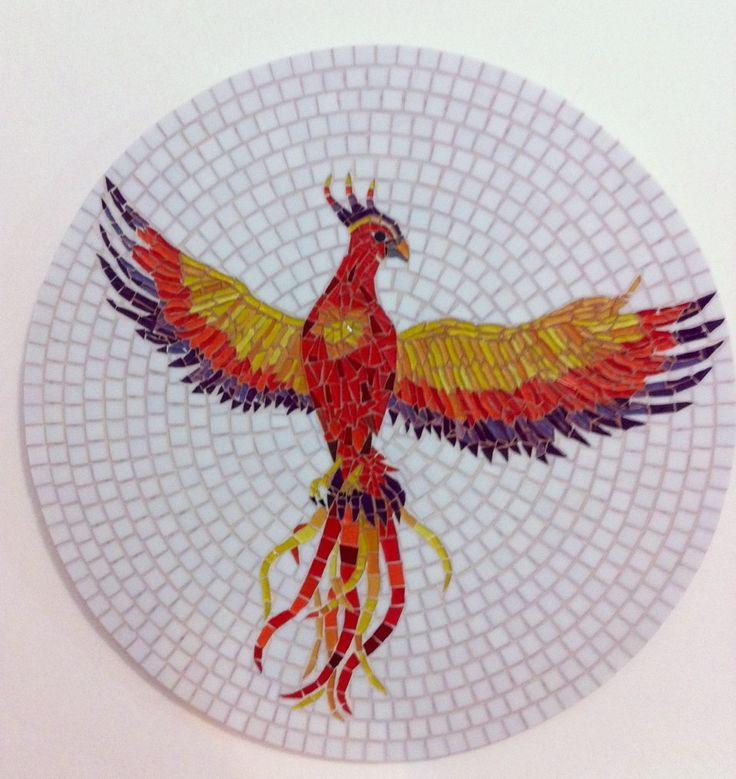 Fênix em mosaico, feita sobre uma base de mdf, que tanto pode ser usada como um quadro ou um tampo de mesa. Trabalhada em pastilhas de vidro e pastilhas cristal. A cor do rejunte e do fundo podem ser alterados.  De origem Etíope, a Fênix é retratada por uma ave sagrada que se ergue das chamas vis...