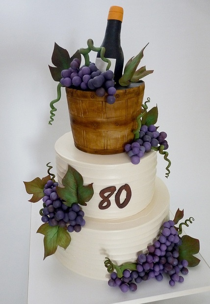 """Wine cake"" iced in buttercream, except for top tier, shaped and covered in fondant. Gumpaste grapes, leaves, vines, and wine bottle."
