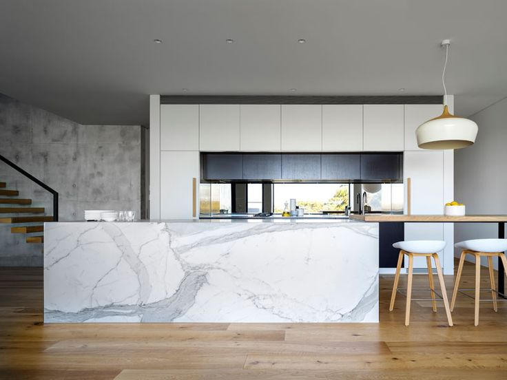 This kitchen pairs white cabinets with a large marble kitchen island, that connects to a wooden bar area with seating.
