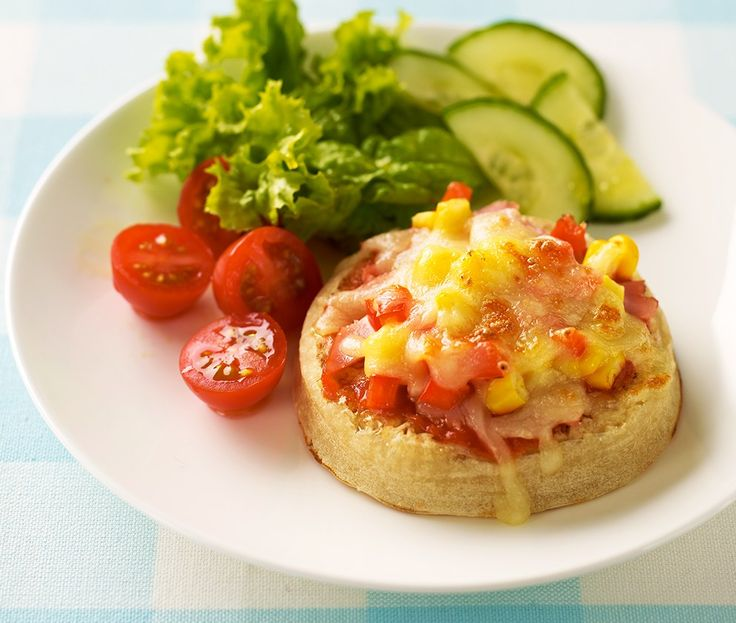 Crumpet topped with tomato and cheese and served with salad