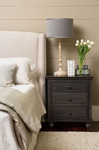 Beautiful bedroom design with mocha walls paint color, wall panels groove walls, ivory wingback headboard with nailhead trim, wood lamp with gray linen lamp shade, espresso stained 3 drawer nightstand, jute rug and linen bedding.