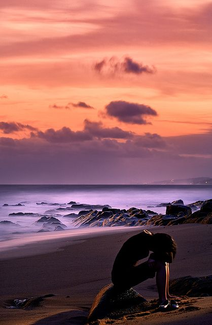 A woman sitting in solitude on an empty beach in Ballito.  South Africa © John and Tina Reid