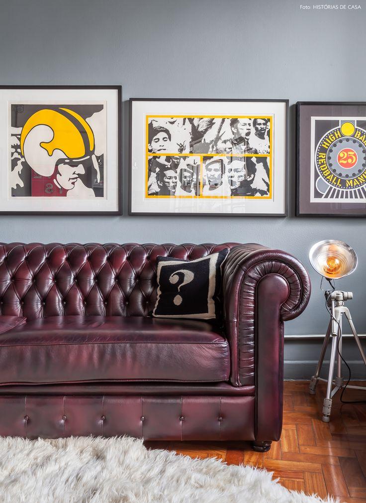 Sofá Chesterfield e parede de quadros decoram a sala de estar do apê.