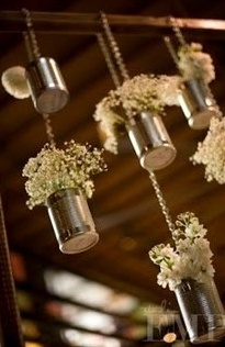 Rustic feel, hanging tin cans with baby's breath.