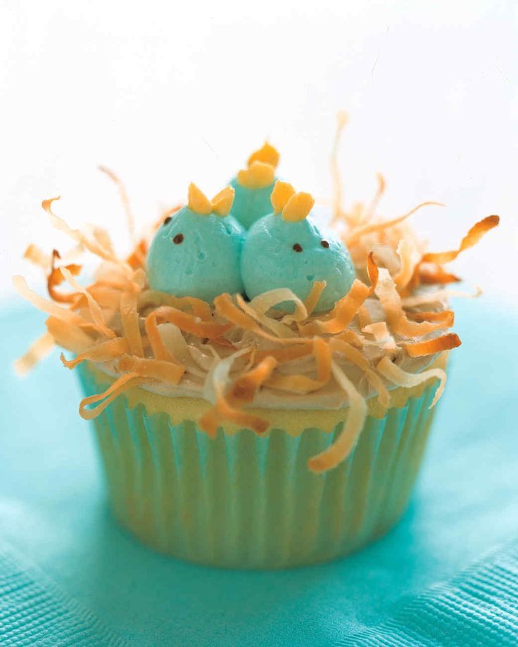 A trio of newborn birds snuggles in a cozy nest of toasted, shredded coconut on top of these picture-perfect cupcakes.