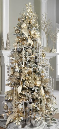 Christmas tree in gold and silver theme with ribbon, ornaments and silk flowers.