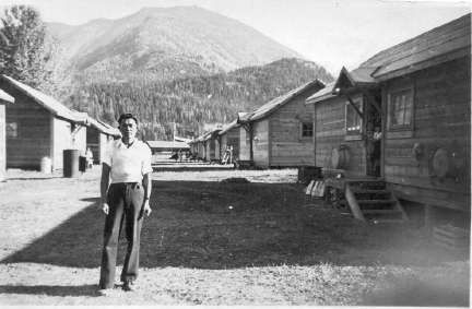 """Nobuo Domai on one of the streets of the internment camp in Lemon Creek, British Columbia, Canada, about 1945. Mr. Domai was a teacher at the Japanese language school. The cabins are the standard two-family model. The internment camps in Canada remained in existence until 1949. After the war, Japanese-Canadians  were given the choice to move east of the Rockies or be repatriated to Japan. 3,964 Japanese Canadians were deported """"back"""" to Japan, a country many of them had never been to before."""