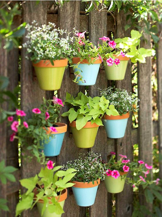 Brightly painted flower pots hung on a backyard fence - so cute!