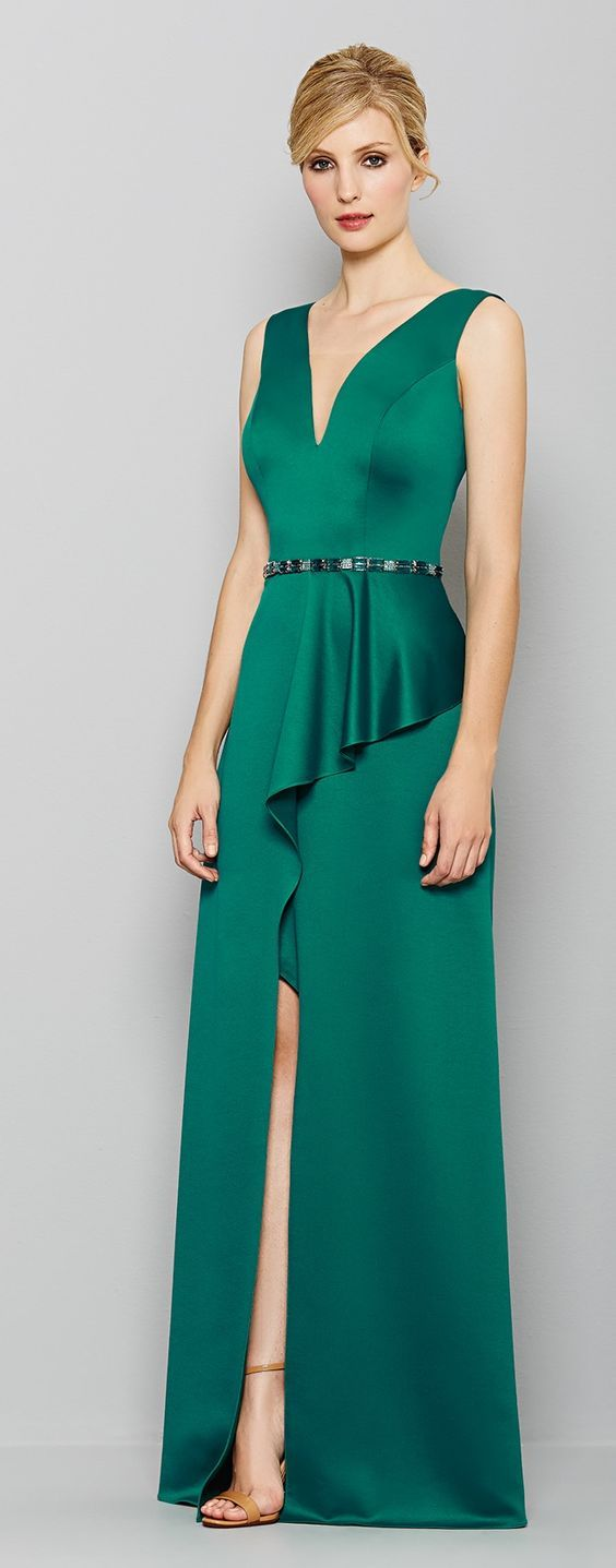 She is a stunner in emerald. Sleeveless plunge neckline with high waist, princess seams and jeweled belt. The beautiful skirt has two panels, one falling in an asymmetrical fabric ruffle over the other, both ending together at floor length. Skirt has a high slit in front. Sexy but not in your face. Style Planet | Kalandra
