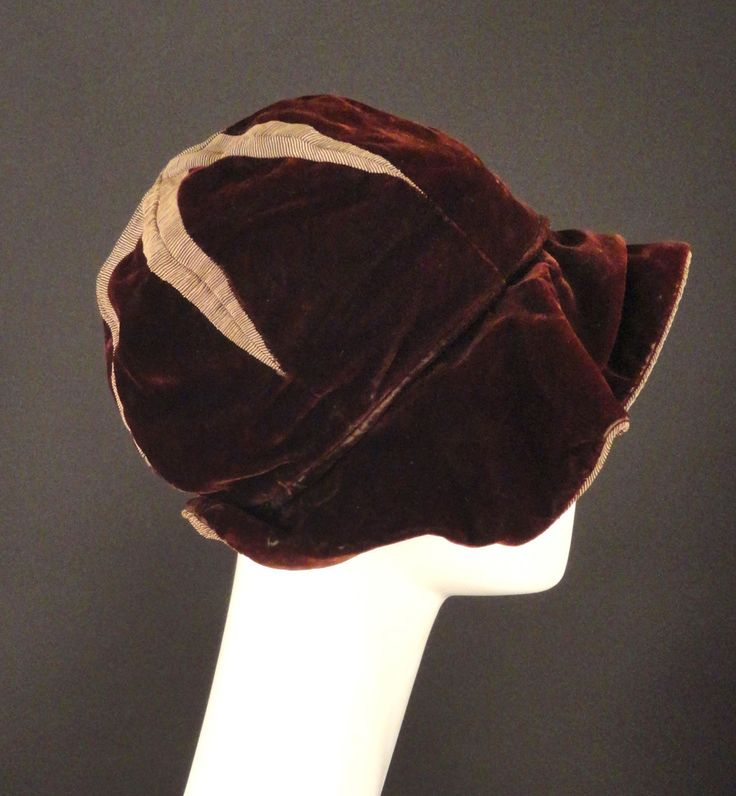 1920s Brown velvet and chestnut brown silk faille cloche. The hat has a floppy brim that has some sculpting with pletas and tacking.  The brim is velvet, the under brim is in the faille.  Deep, pie wedge crown with a large starburst of silk failed on the top.The cloche is lined in black velvet and silk.
