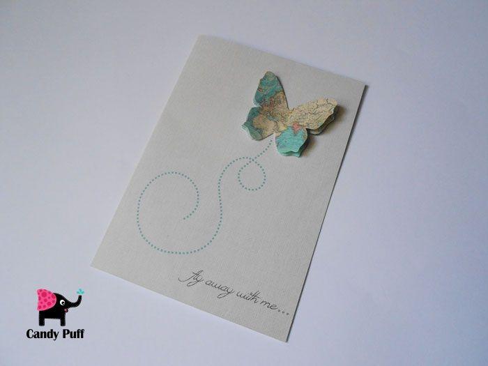 """Postal  em tons cinza que contém uma borboleta tridimensional criada a partir de um mapa. Na capa do postal existe a afirmação: """"fly away with me""""."""
