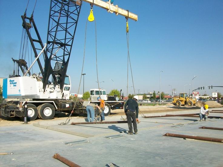 Crane hoisting 80,000-pound concrete panels into place for Nampa wash construction