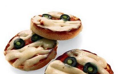 Pizzette zombie - Le pizzette zombie sono degli antipasti da preparare per il buffet di Halloween per la festa dei bambini. In pochi minuti saranno pronte, utilizzando pasta sfoglia, olive, formaggio per pizza e salsa di pomdoro.