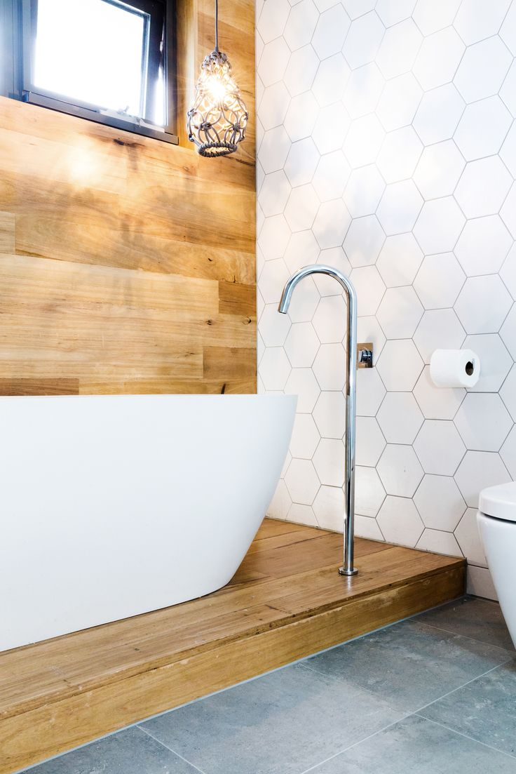 Gorgeous bathroom!! Timber feature panelling behind free standing bath, white hexagon tiles and grey floor tiles Bec & George