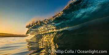 Sunrise glints yellow on breaking wave, dawn surf, The Wedge, Newport Beach, California