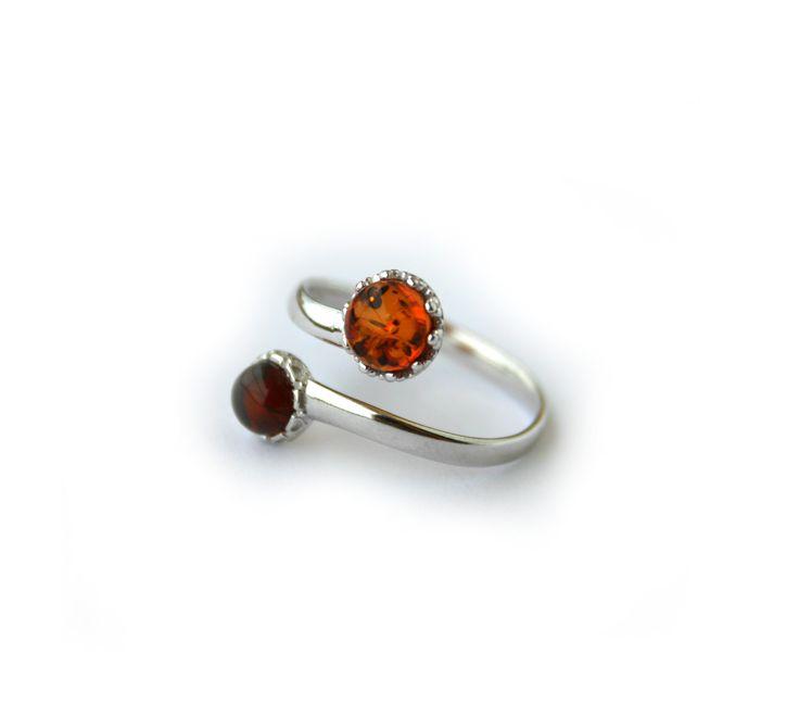 Originale e raffinato anello contrarié con due gemme orlate da un pizzo in argento. La pietra più grande è di color marrone chiaro e la più piccola rosso marrone. Montatura finemente lavorata in Argento 925 rodiato.