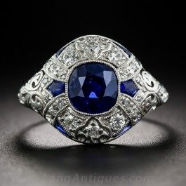 Hand-fabricated in platinum circa 1925, this classic 'cigar style' ring features a natural, no-heat cushion-cut sapphire of Pailin, Cambodian origin, whose velvety quality and cobalt blue most resemble the rare, prized sapphires from Kashmir. The 1.50 carat stone centers milgrained diamond-set ribbons accented with 6 fancy-cut sapphires. An exceptional vintage beauty, but too delicate for everyday wear. Currently ring size 5 1/2, with sizing limited to one size up or down.