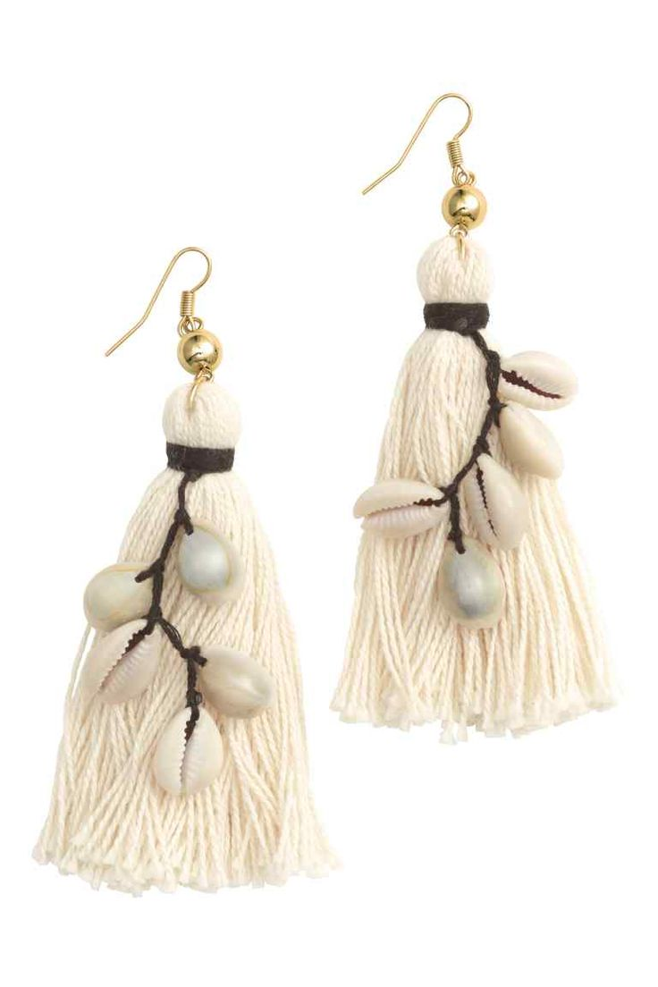 Oorbellen met schelpjes: Een paar metalen oorbellen die versierd zijn met schelpjes, kunststof kralen en een groot kwastje van textiel. Lengte 11 cm.