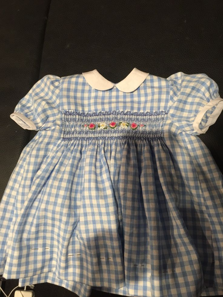 A smocked gingham dress I made for my granddaughter. It's accented with pearl beads and bullion roses