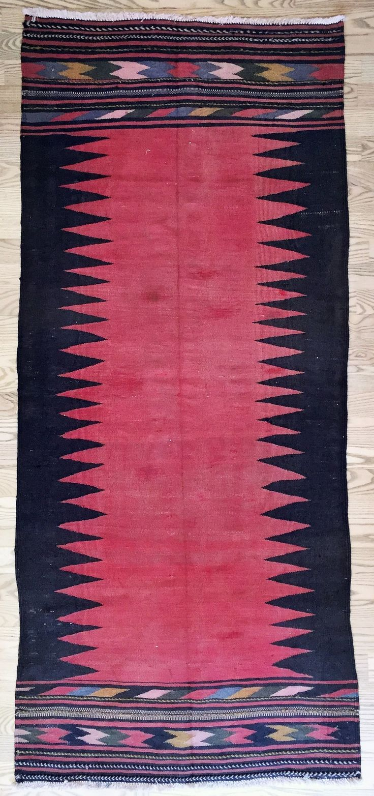 Denne Soufreh er en brændt rød kelim (fladvævet) med et sort zigzagmotiv på hver langside og for enderne forskellige mønstre i hvide, sorte, blå, karrygule og røde farver samt med broderede striber. Tæppet er vævet af kurdiske stammer i Iran af fåreuld på en bomuldstrend. Vintage: 60-80 år Størrelse: 195*115 cm