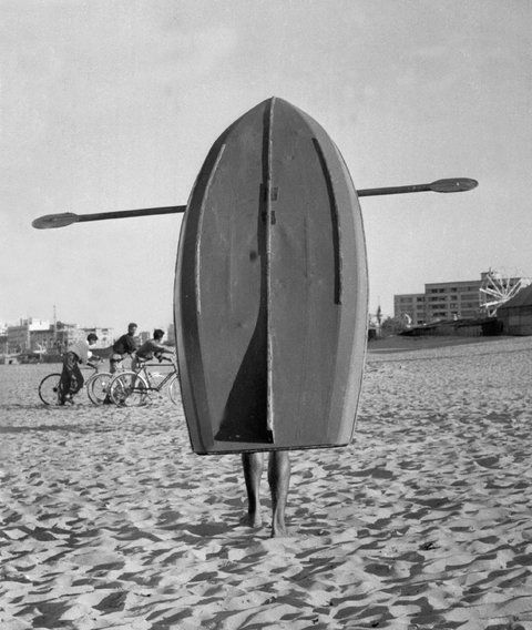 Jürgen Schadeberg. MAN CARRYING A ROWING BOAT ON THE BEACH, DURBAN 1961. Silver print, 26.5 x 33.5cm.