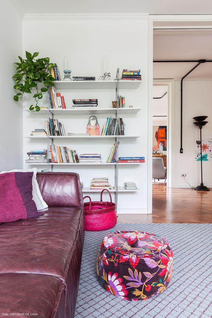 Sala de televisão tem sofá em couro e acessórios nos tons de roxo e rosa.