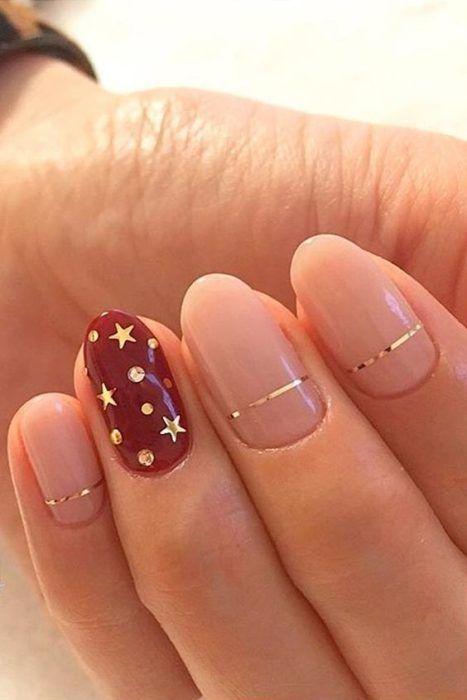 Decoración de uñas navideñas en color nude y guinda