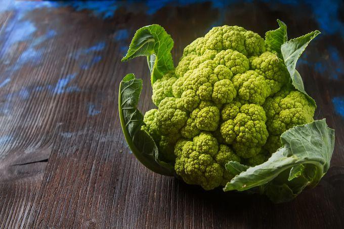 Ripe green cauliflower with leaves. Dark wood background. by Naltik on…