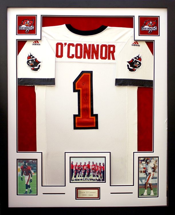 football jersey displayed with custom cut openings for photographs patches and a personalized plate designed and framed at art frame express nj ms