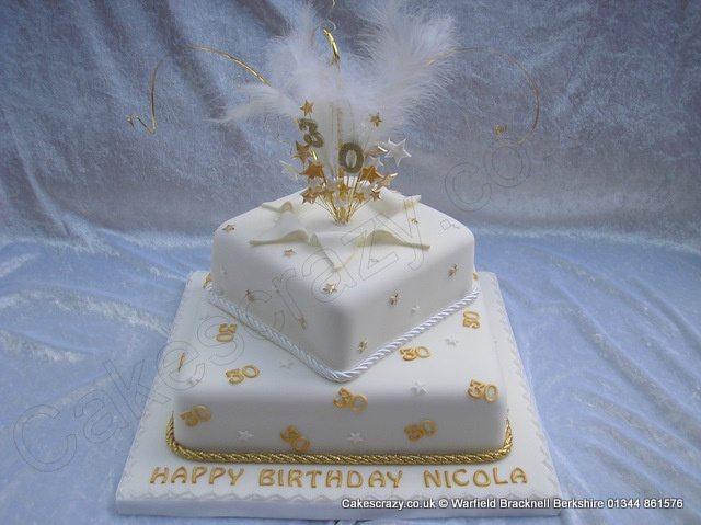 Square two tier celebration birthday cake in white icing with gold stars and number 30. Finished with a white satin and gold rope ribbon topped with an explosive feather topper coloured in gold and white. Glitter number 30