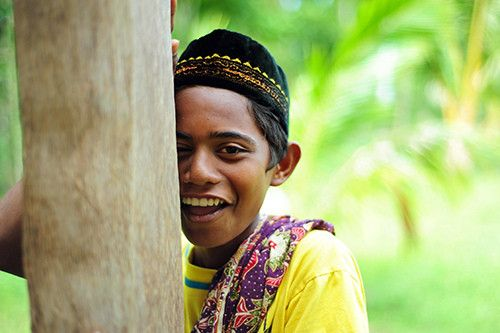 Young boy (aneuk agam Aceh) in traditional dress smiling and hiding behind tree. (Photo by Anthony Asael/flickr.com/photos/anthonyasael)