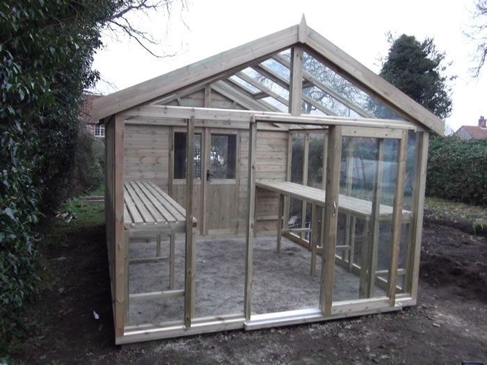 a tailor made greenhouse potting shed in cladding with a range of features including staging roof vents and full length glass windows