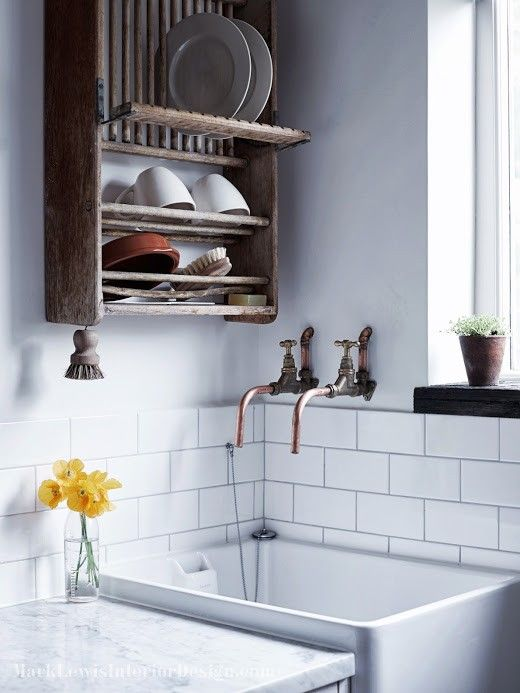 Unique, rustic kitchen or laundry room design featuring white subway tile backsplash, farmhouse sink, vintage plate rack and marble countertops | Mark Lewis Interior Design